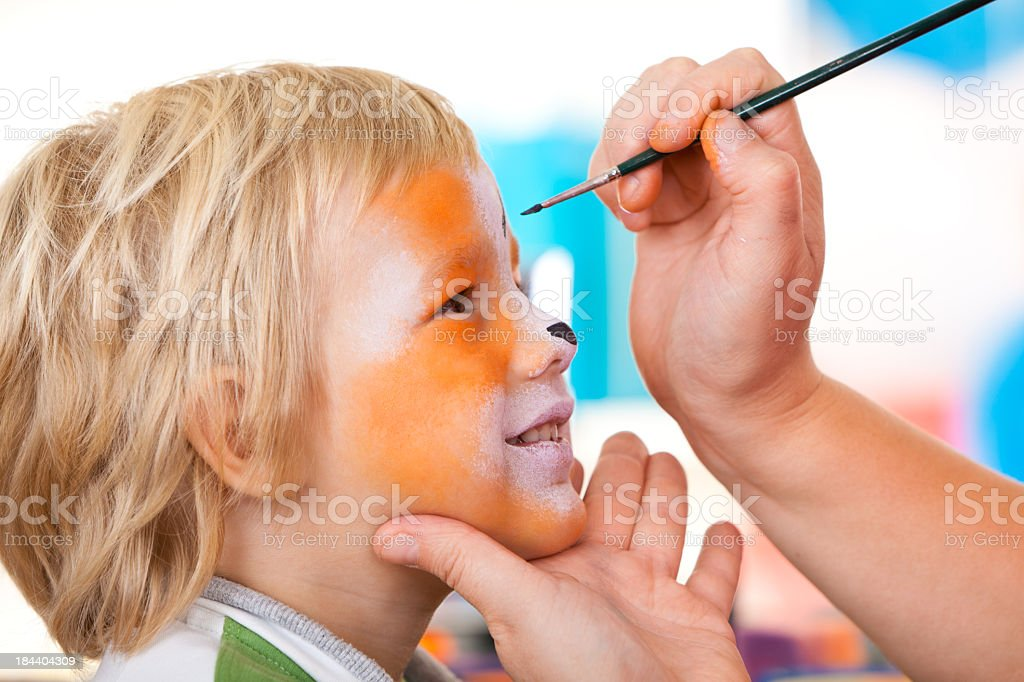 Little boy having face painted on birthday party stock photo