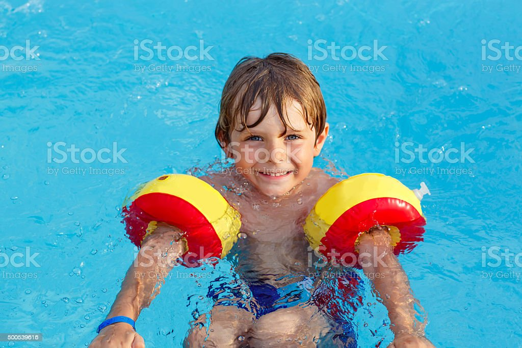 little boy having fun in an swimming pool stock photo