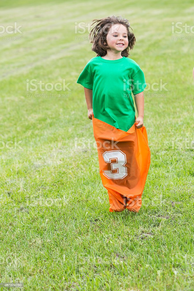 Little boy having fun in potato sack race stock photo