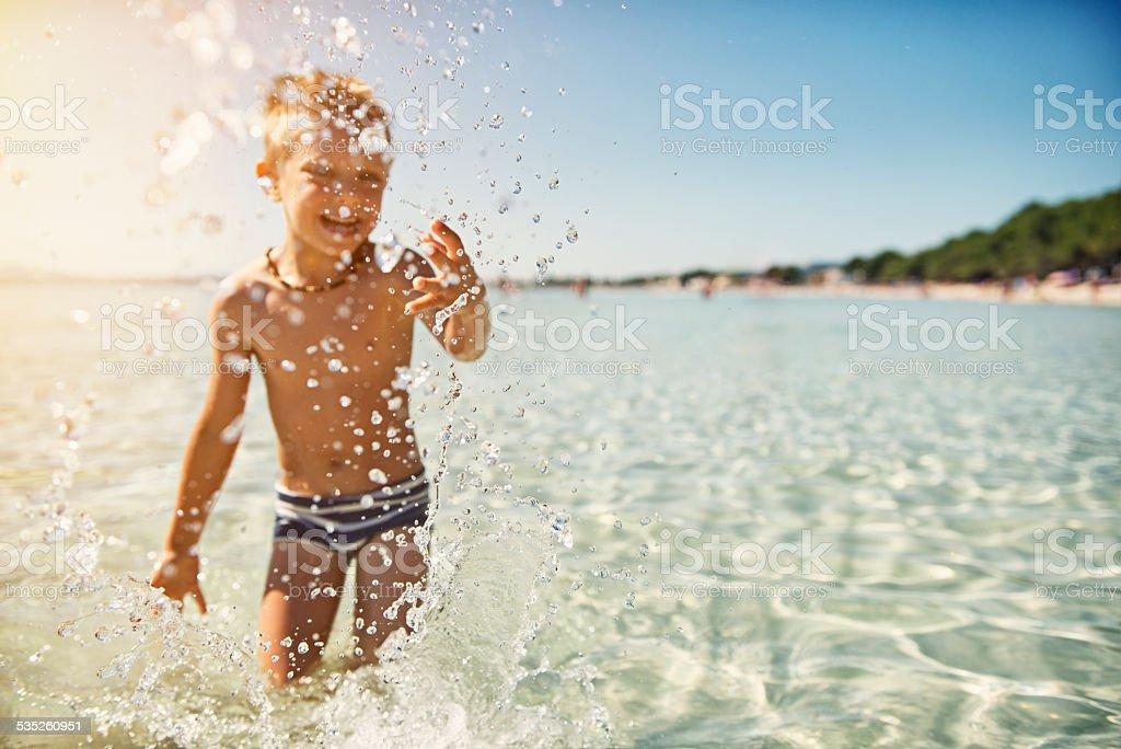Little boy having fun in sea splashing stock photo