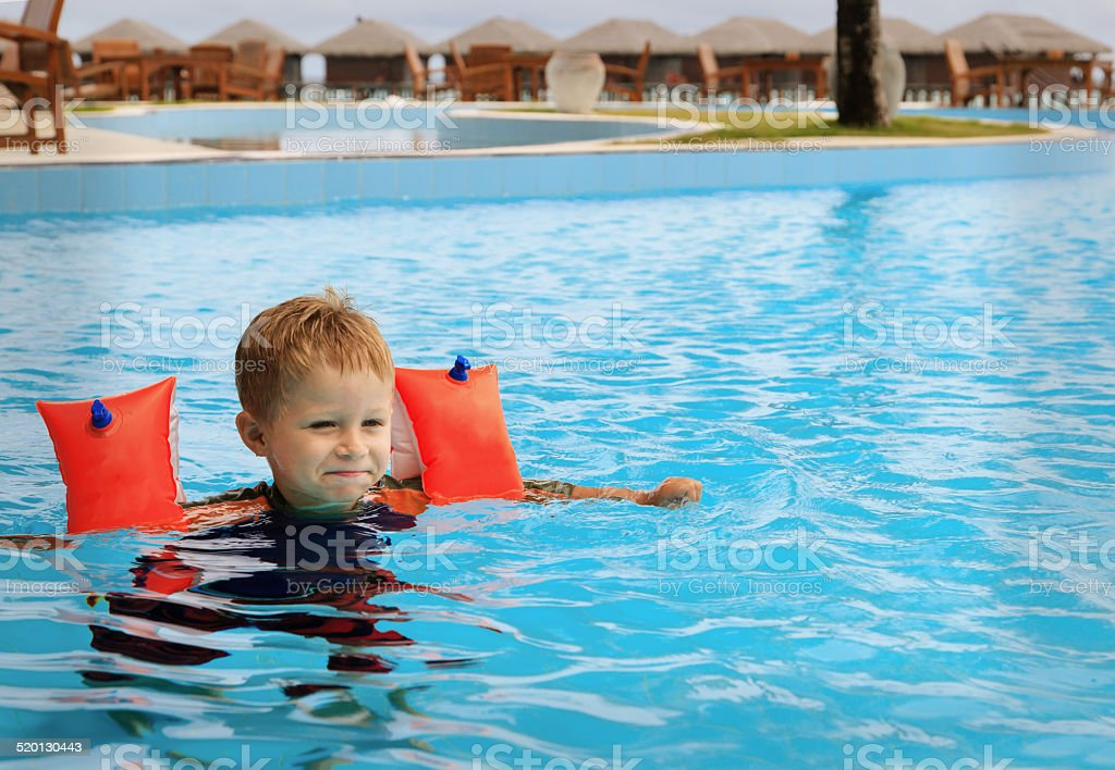 little boy having fun in the swimming pool stock photo