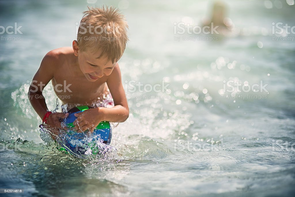 Little boy having fun playing ball in sea stock photo