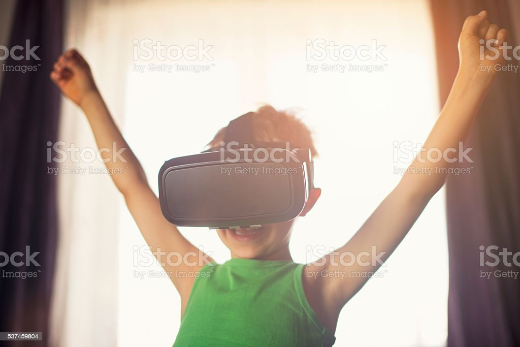 Little boy having fun playing with virtual reality headset stock photo