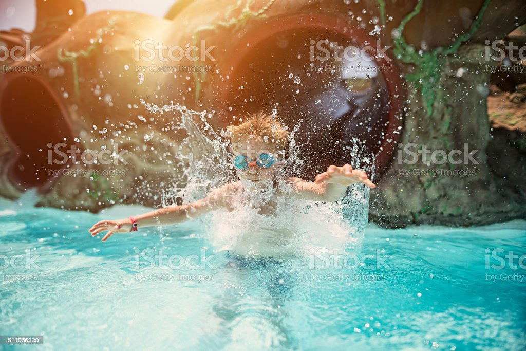 Little boy having fun sliding in water park stock photo