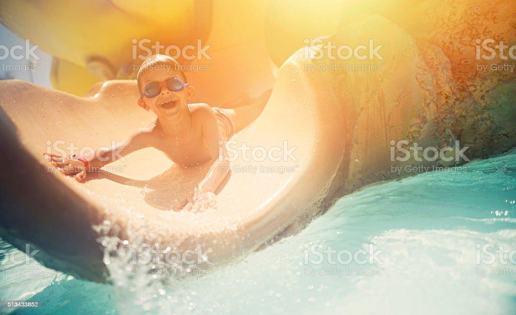 Little boy having fun sliding in water park stock photo