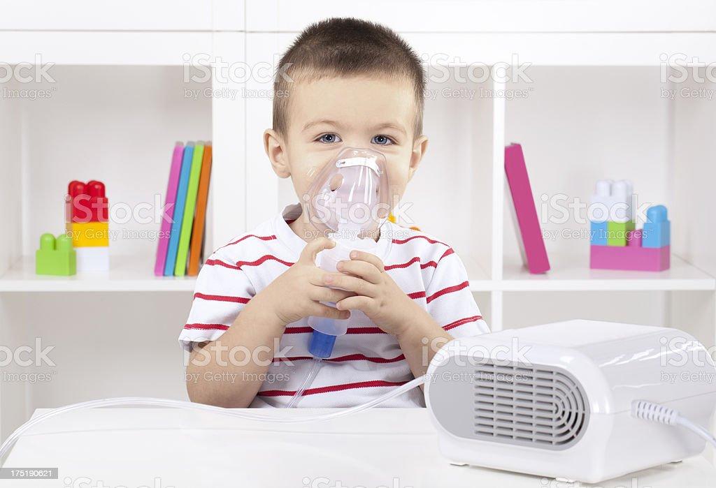 Little boy having inhalation at home stock photo