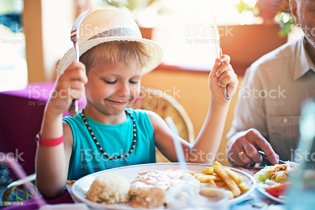 Little boy having meal at restaurant stock photo