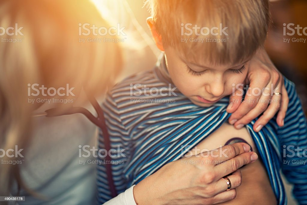 Little boy having medical examination at home stock photo