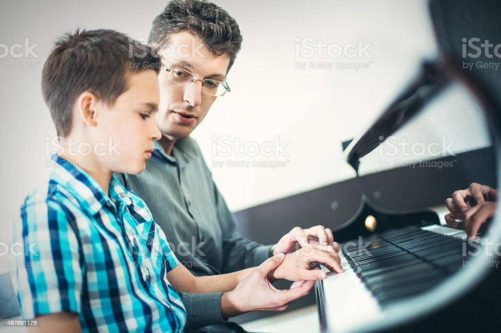 Little boy having piano lesson. stock photo