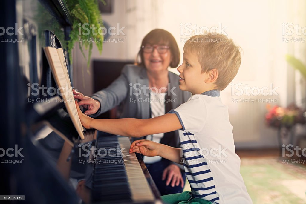 Little boy having piano lesson stock photo