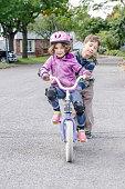 Little boy helping his sister biking