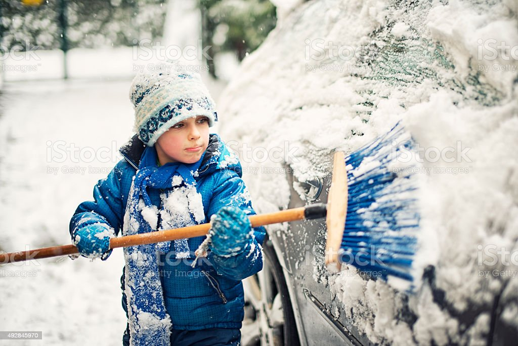 Little boy helping to clean family car after winter attack stock photo