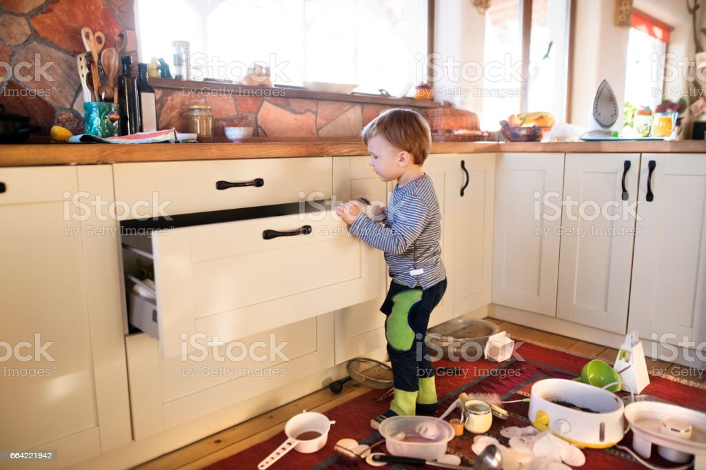 Little boy helping with house chores, organizing kitchen drawer stock photo