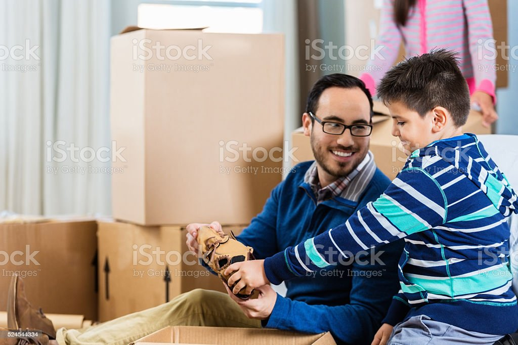 Little boy helps father unpack box stock photo