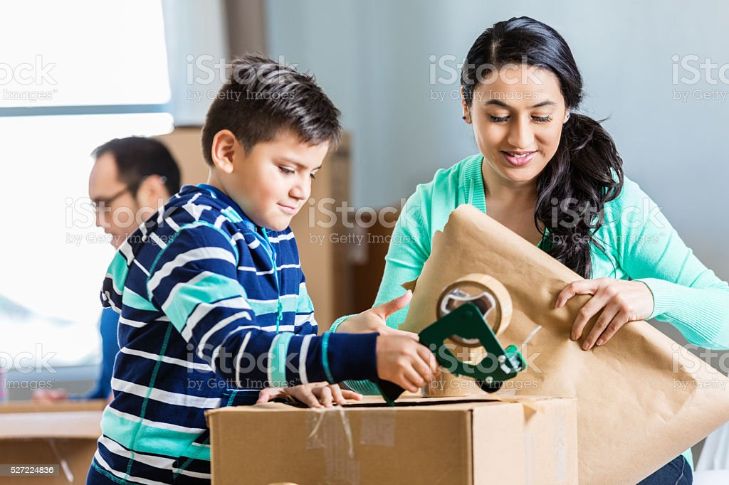 LIttle boy helps his mother pack cardboard box stock photo