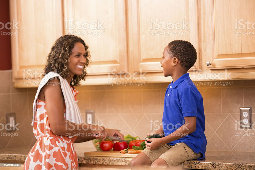 Little boy helps mom with healthy dinner salad. Vegetables, kitchen. stock photo