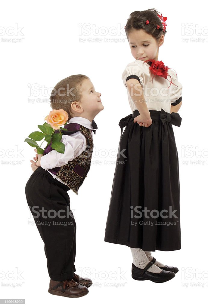 Little boy hides from the girl a yellow rose stock photo