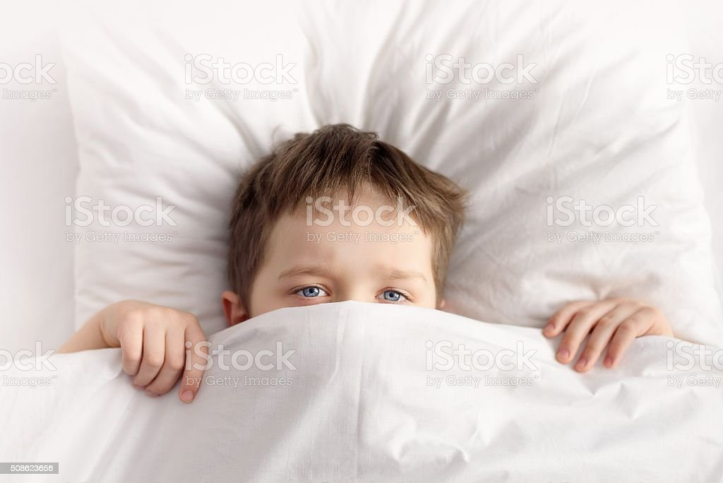 Little boy hiding in bed under the blanket at home stock photo