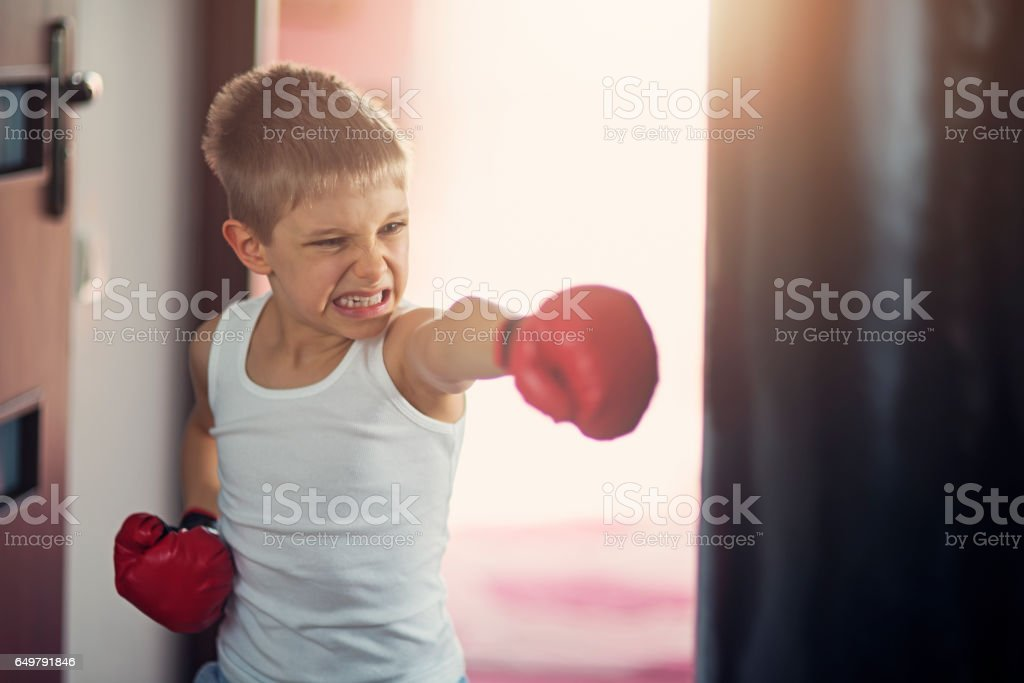 Little boy hitting hard punching bag stock photo
