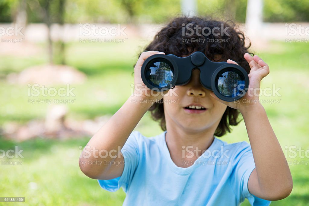 Little boy holding a binocular at park stock photo