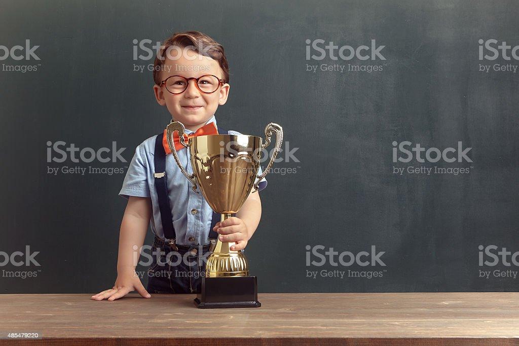 Little boy holding a golden trophy stock photo