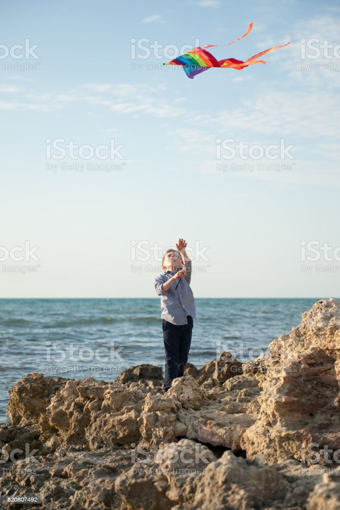 Little boy holding a kite standing on a rock against the sea stock photo