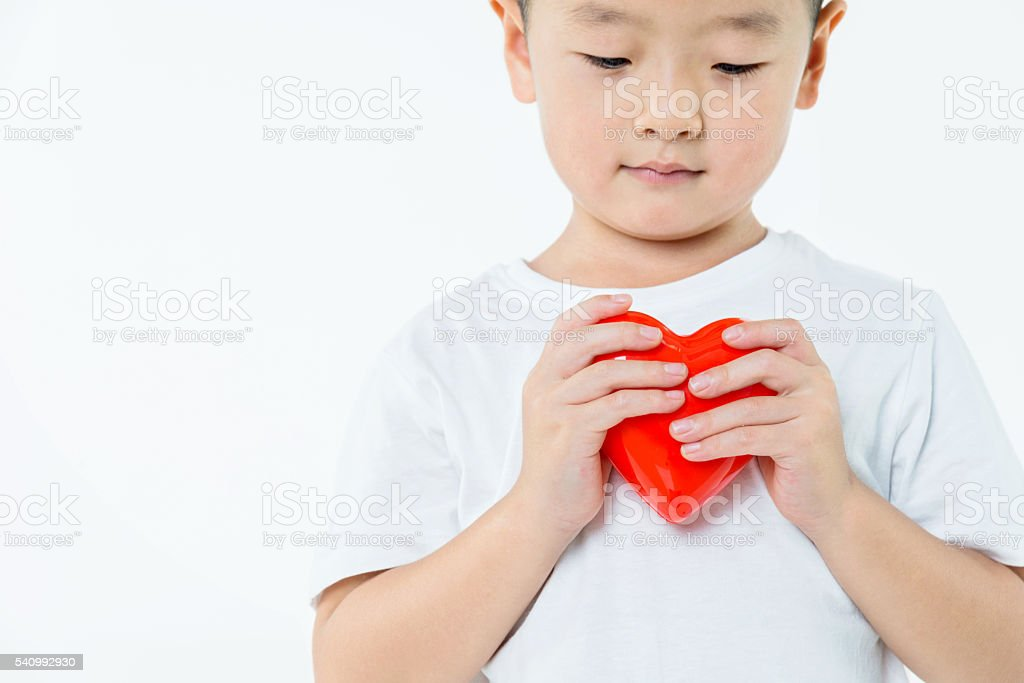 Little boy holding a red heart stock photo