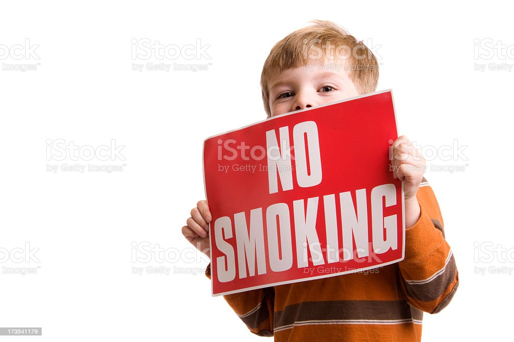 Little boy holding a red sign that says NO SMOKING stock photo