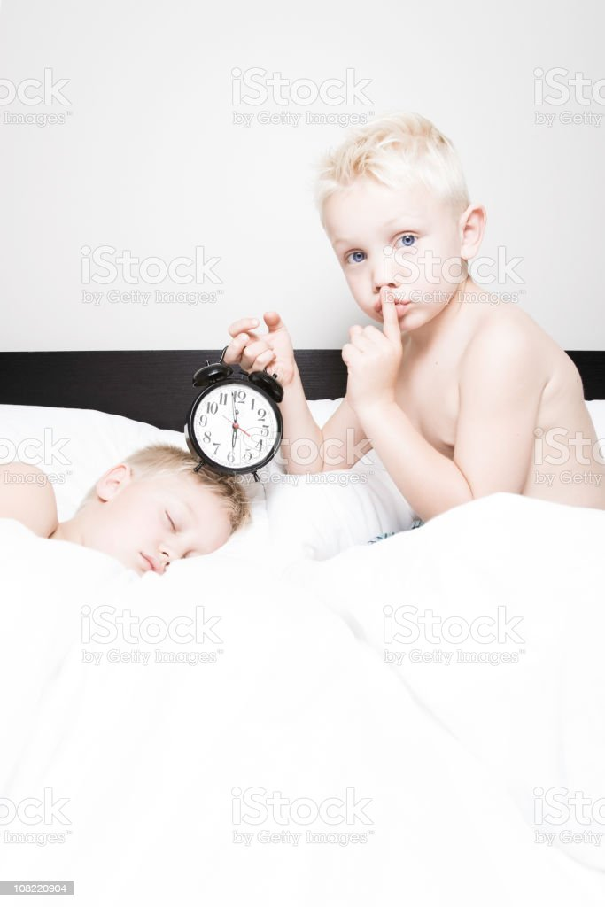 Little Boy Holding Alarm Clock to Sleeping Brother royalty-free stock photo