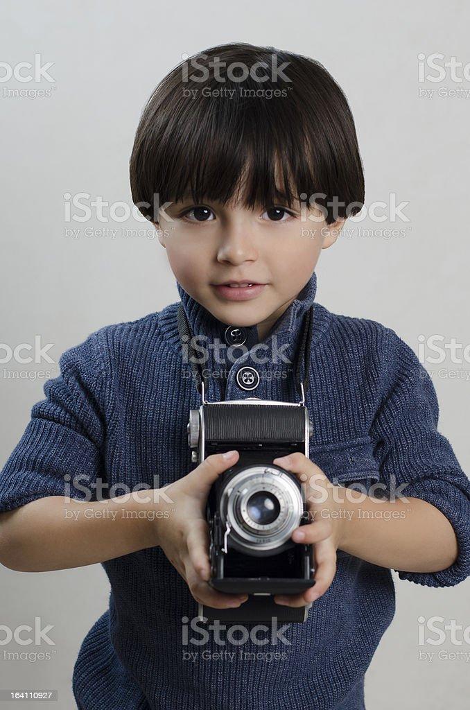Menino, segurando uma câmera antiga foto royalty-free
