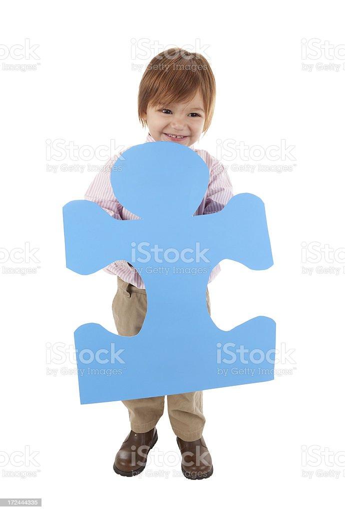 Little Boy Holding Blue Puzzle Piece stock photo