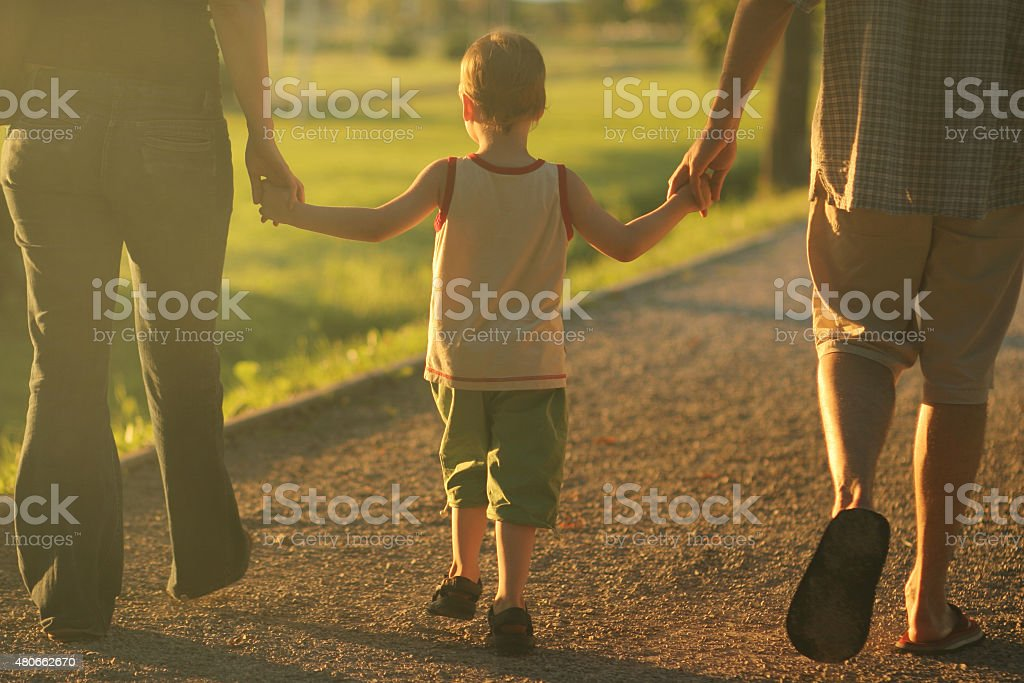 Little boy holding hands with his family walking at sunset stock photo