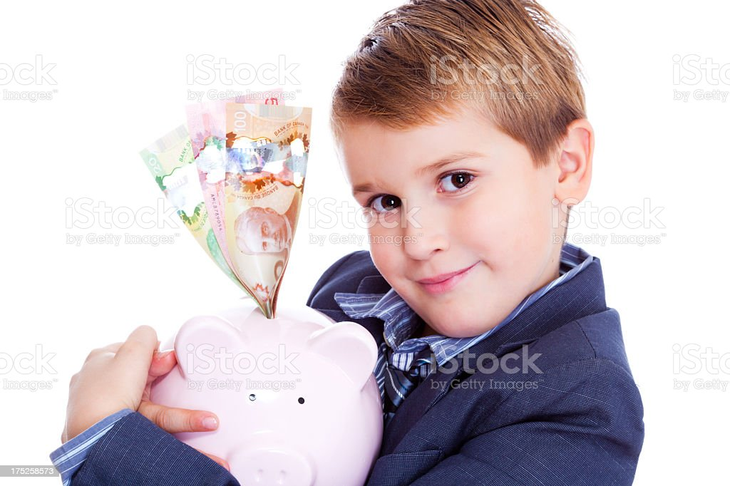 Little Boy Holding Piggy Bank with Canadian Dollars royalty-free stock photo