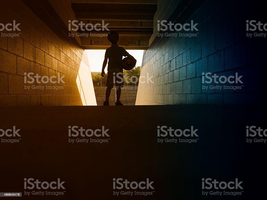 Little Boy Holding Soccer Ball In Stadium stock photo