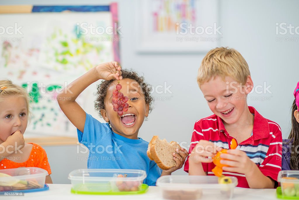 Little Boy Holding up His Grapes stock photo