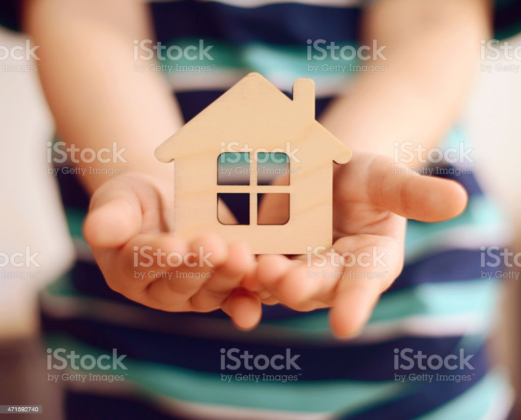 little boy holds in hands small toy house stock photo