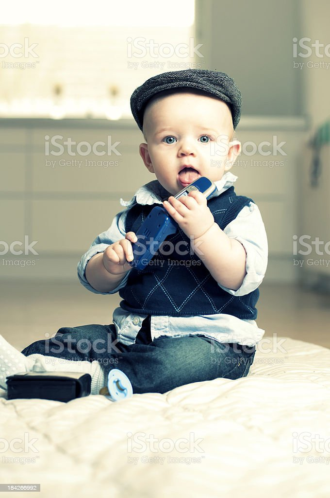 Little boy holds mobile phone stock photo