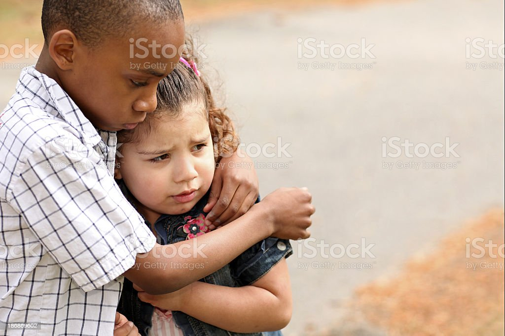 Little boy hugging a little girl to protect her stock photo