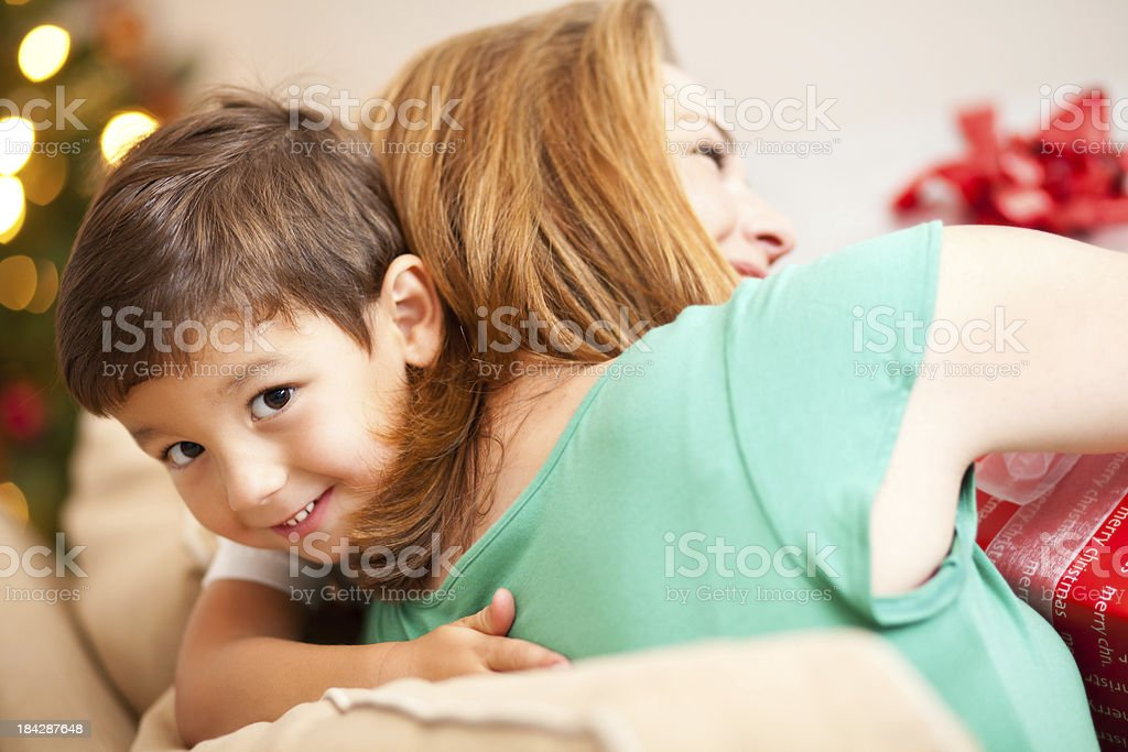 Little Boy Hugging Mother on Christmas Morning royalty-free stock photo