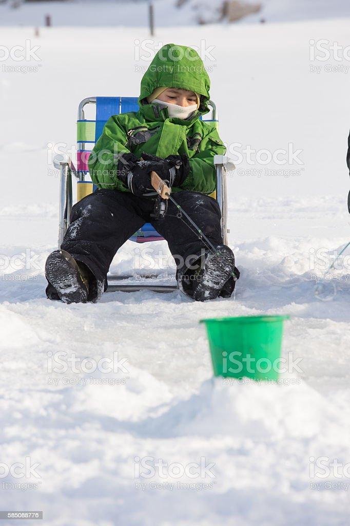 Little boy ice fishing stock photo
