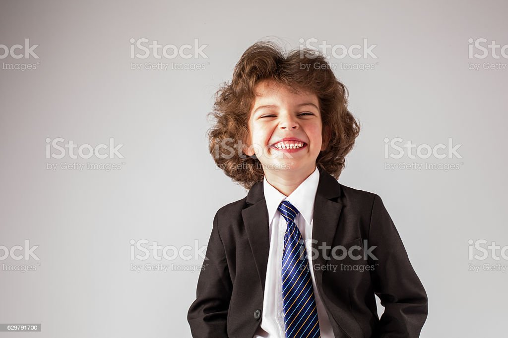 Little boy in a business suit laughing eyes narrowed. stock photo