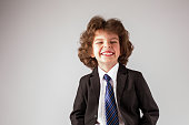 Little boy in a business suit laughing eyes narrowed.