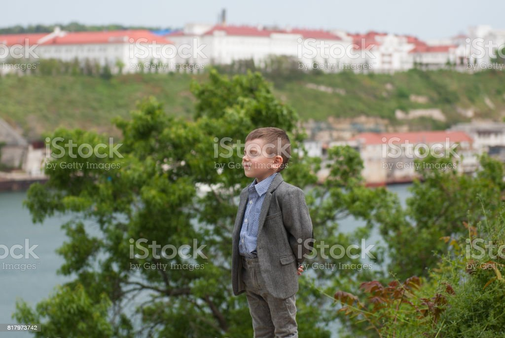 Little boy in a jacket on a background of trees and a city stock photo