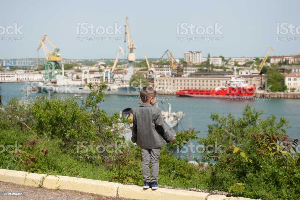 little boy in a jacket stands against the background of a seaport stock photo