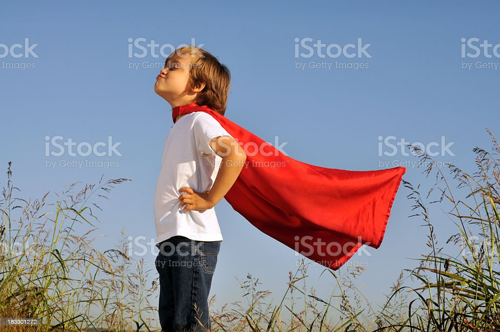 A little boy in a red superhero cape playing outside stock photo