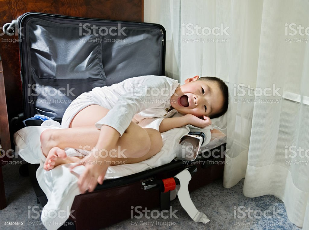 Little boy in a suitcase stock photo