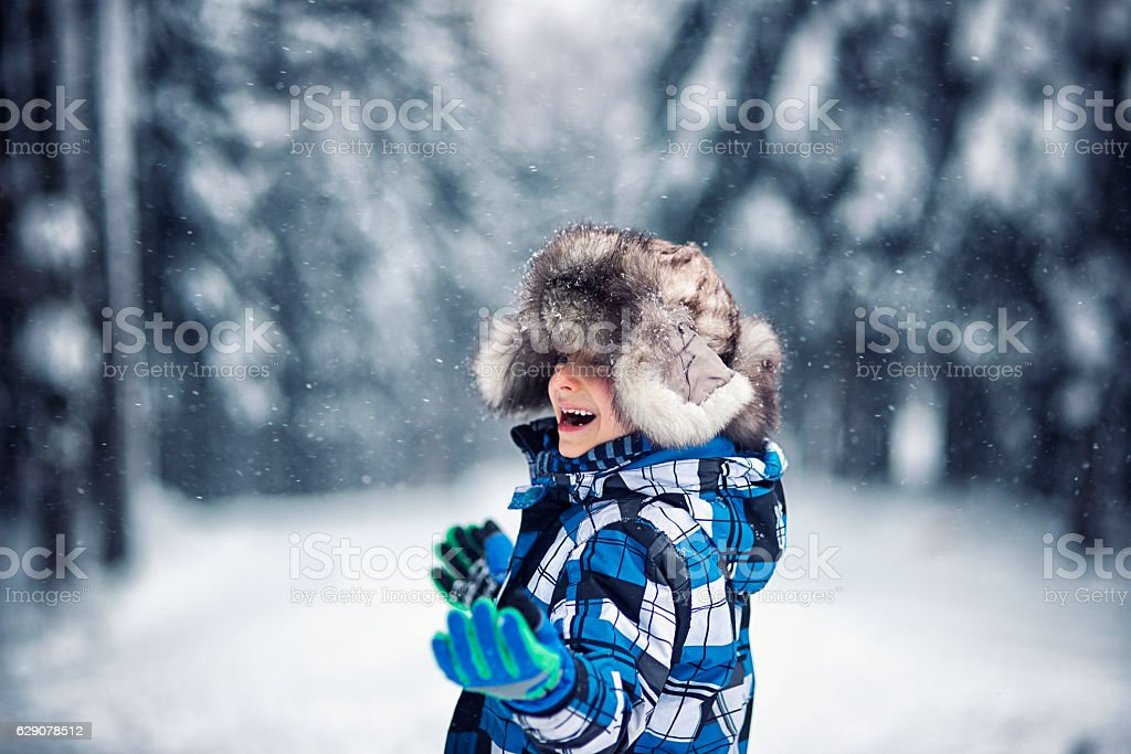 Little boy in big fur cap enjoying the first snow stock photo