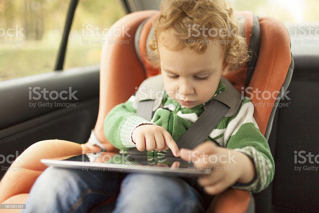 Little boy in child seat using his digital tablet royalty-free stock photo