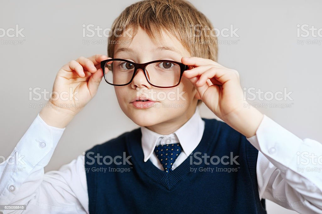 little Boy in eyeglasses in a white shirt, tie and stock photo