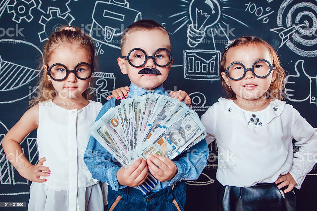 Little boy in glasses and mustache on dark background with stock photo